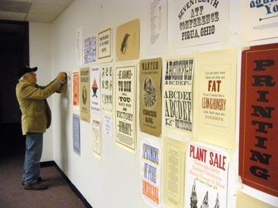 man hanging posters